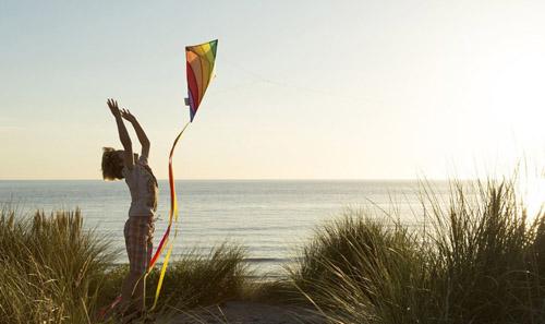 Kid throwing kite off dune